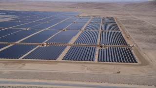 AX0005_090 - 5K stock footage aerial video orbit a large solar energy array in the Mojave Desert, California