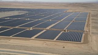 AX0005_090E - 5K stock footage aerial video orbit a large solar energy array in the Mojave Desert, California
