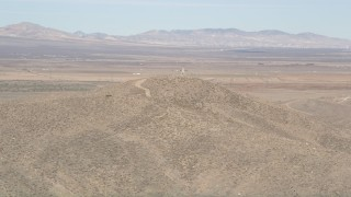 AX0005_096 - 5K stock footage aerial video of orbiting a building atop a desert mountain overlooking Antelope Valley, California