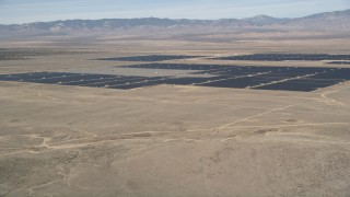 AX0005_097 - 5K stock footage aerial video of fly over desert mountain and reveal solar energy array in the Mojave Desert, California