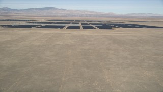 AX0005_100 - 5K stock footage aerial video fly over desert hill to reveal vast solar energy array in Antelope Valley, California
