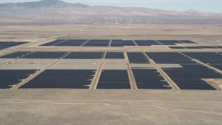 AX0005_102 - 5K stock footage aerial video fly low over desert hill and reveal solar array in Antelope Valley, California