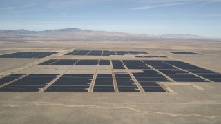 AX0005_103 - 5K stock footage aerial video approach Mojave Desert solar energy array in California