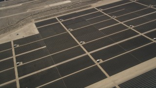 AX0005_110 - 5K stock footage aerial video orbiting panels at a Mojave Desert solar array in California
