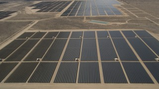 AX0005_113 - 5K stock footage aerial video approach and fly over solar panels at an array in the Mojave Desert, California