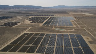 AX0005_118 - 5K stock footage aerial video approach and fly over panels in a solar energy array in the Mojave Desert, California