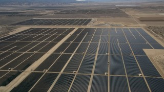 AX0005_119E - 5K stock footage aerial video approach and fly over Mojave Desert solar energy array in California