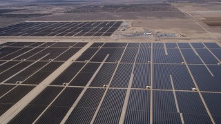 AX0005_120 - 5K stock footage aerial video of flying over rows of solar panels at a desert array in Antelope Valley, California
