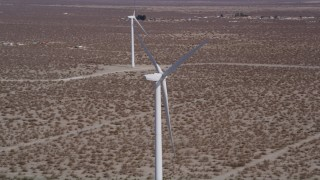 AX0005_129 - 5K stock footage aerial video orbit top of a windmill in the Mojave Desert, California