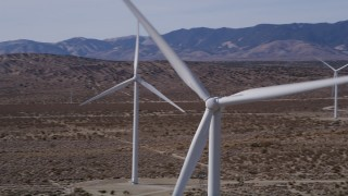 AX0005_131 - 5K stock footage aerial video orbit of a windmill at a desert wind farm in Antelope Valley, California