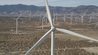 AX0005_131E - 5K stock footage aerial video orbit of a windmill at a desert wind farm in Antelope Valley, California