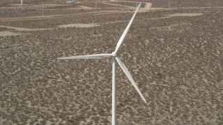 AX0005_135 - 5K stock footage aerial video of a windmill with spinning blades in the Mojave Desert, California