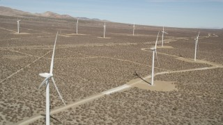 AX0005_139 - 5K stock footage aerial video fly over a row of windmills at a desert wind farm in California