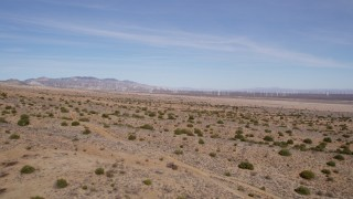 AX0006_004 - 5K stock footage aerial video fly over desert plants toward wind farm in Antelope Valley, California