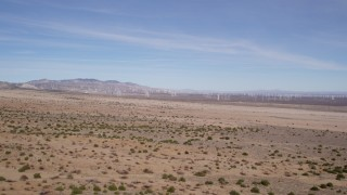 AX0006_005 - 5K stock footage aerial video fly over desert vegetation toward a distant wind farm in Antelope Valley, California