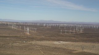 AX0006_006 - 5K stock footage aerial video pan across rows of windmills at desert wind farm in Antelope Valley, California