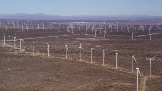 AX0006_008 - 5K stock footage aerial video pan to line of windmills at large wind farm in the Mojave Desert, California