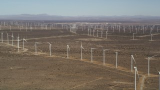 AX0006_008E - 5K stock footage aerial video pan to line of windmills at large wind farm in the Mojave Desert, California