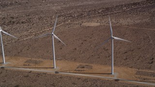 AX0006_011 - 5K stock footage aerial video of orbiting a pair of windmills in the desert in Antelope Valley, California