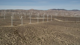 AX0006_013 - 5K stock footage aerial video approach a row of windmills at a wind farm in the Mojave Desert, California