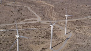 AX0006_016 - 5K stock footage aerial video of flyby a trio of windmills at a wind farm in the Mojave Desert, California