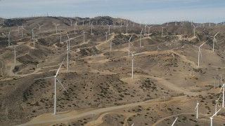 AX0006_019 - 5K stock footage aerial video approach large group of windmills at desert wind energy farm in Antelope Valley, California
