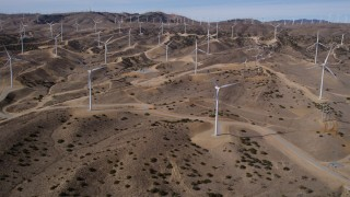 AX0006_020 - 5K stock footage aerial video of approaching a field full of windmills at a desert wind farm in Antelope Valley, California