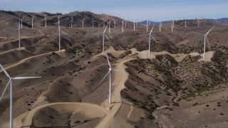 AX0006_022 - 5K stock footage aerial video of approaching windmills at a desert wind energy farm in Antelope Valley, California