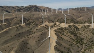 AX0006_022E - 5K stock footage aerial video of approaching windmills at a desert wind energy farm in Antelope Valley, California