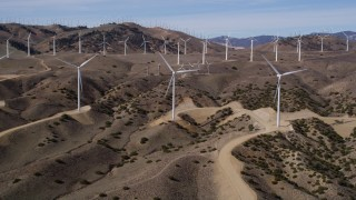 AX0006_023 - 5K stock footage aerial video approaching a pair of windmills at a wind energy farm in the Mojave Desert of California