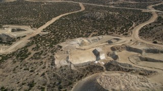 AX0006_028 - 5K stock footage aerial video fly over a small quarry at a wind farm in the Mojave Desert, California