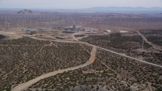 AX0006_029 - 5K stock footage aerial video approach quarry surrounded by wind farm windmills in the Mojave Desert, California