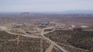 AX0006_030 - 5K stock footage aerial video orbit a quarry by a field of windmills in the Mojave Desert, California