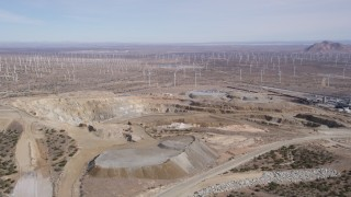 AX0006_031 - 5K stock footage aerial video orbiting a desert quarry by a wind farm in Antelope Valley, California