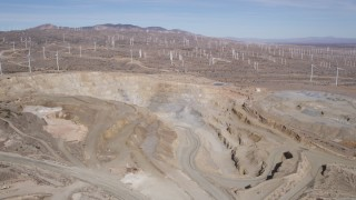 AX0006_033 - 5K stock footage aerial video orbiting a quarry pit by a field of windmills in the Mojave Desert, California