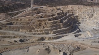 AX0006_035 - 5K stock footage aerial video orbiting the pit of a desert quarry in the Mojave Desert, California