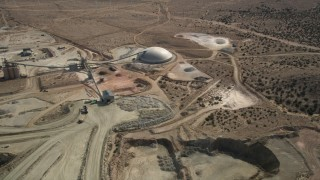 AX0006_037 - 5K stock footage aerial video orbiting above quarry buildings in the Mojave Desert, California