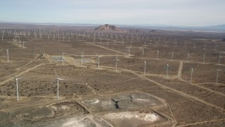 AX0006_039 - 5K stock footage aerial video approach a wind energy farm with rows of windmills in the Mojave Desert, California
