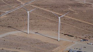 AX0006_046 - 5K stock footage aerial video approach a couple of windmills at a desert wind energy farm in California