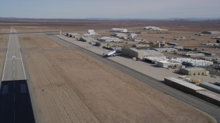 AX0006_055 - 5K stock footage aerial video pan to airliner by hangar at Mojave Air and Space Port in California