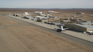 AX0006_055E - 5K stock footage aerial video pan to airliner by hangar at Mojave Air and Space Port in California