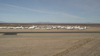 AX0006_057 - 5K stock footage aerial video of a low altitude orbit of planes at an aircraft boneyard in the desert, Mojave Air and Space Port, California