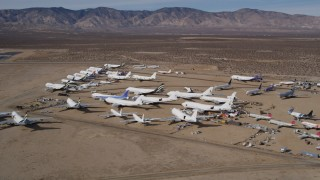AX0006_059 - 5K stock footage aerial video orbit group of airplanes at an aircraft boneyard in the California desert, Mojave Air and Space Port