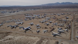 AX0006_061 - 5K stock footage aerial video orbiting an aircraft boneyard in the Mojave Desert, California