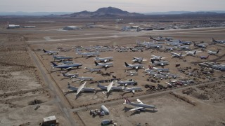AX0006_062 - 5K stock footage aerial video of circling an aircraft boneyard in the Mojave Desert of California