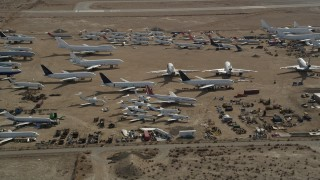 AX0006_063 - 5K stock footage aerial video orbiting jet aircraft at an airplane boneyard in the Mojave Desert, California