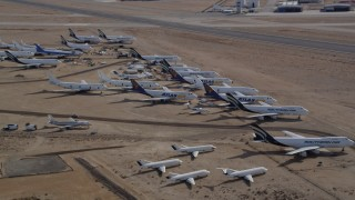 AX0006_064 - 5K stock footage aerial video orbit a group of aircraft at a boneyard in the Mojave Desert, California