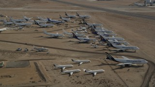 AX0006_064E - 5K stock footage aerial video orbit a group of aircraft at a boneyard in the Mojave Desert, California
