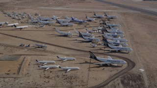 AX0006_065 - 5K stock footage aerial video orbit large group of aircraft at a desert boneyard in California's Mojave Desert