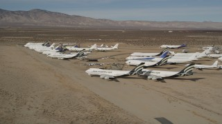 AX0006_068 - 5K stock footage aerial video of jet aircraft at a desert boneyard in California's Mojave Desert
